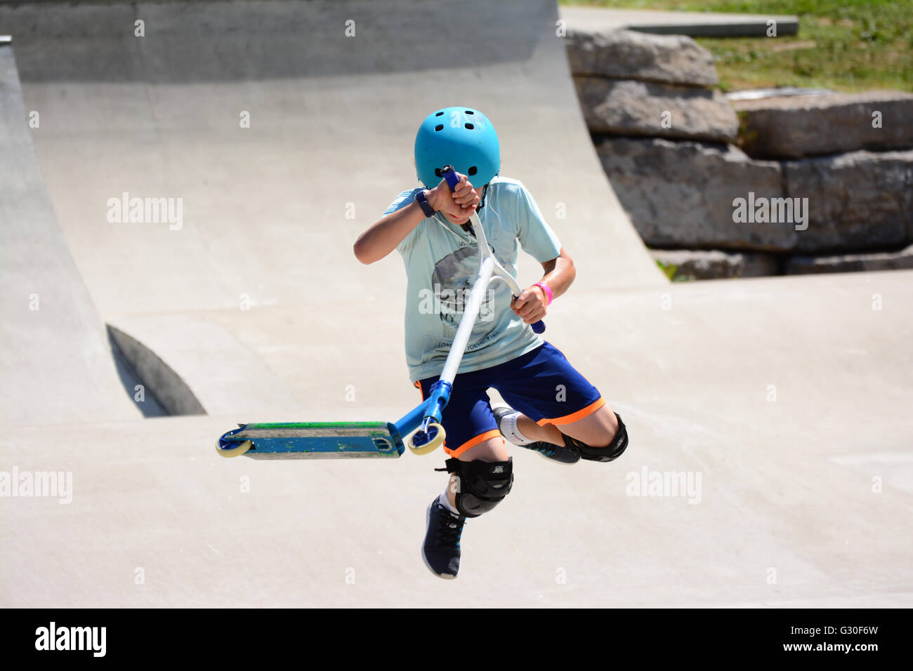 Extreme ride on scooter in skate park - Stock Image