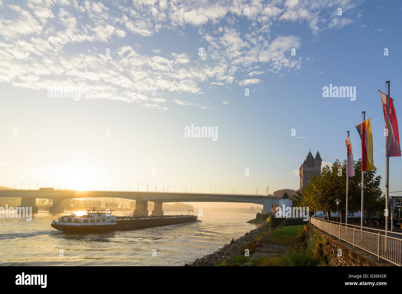 river Rhein (Rhine) at sunrise with Nibelungenbrücke , Nibelungen tower , cargo ship, Germany, Rhineland-Palatinate, - Stock Image