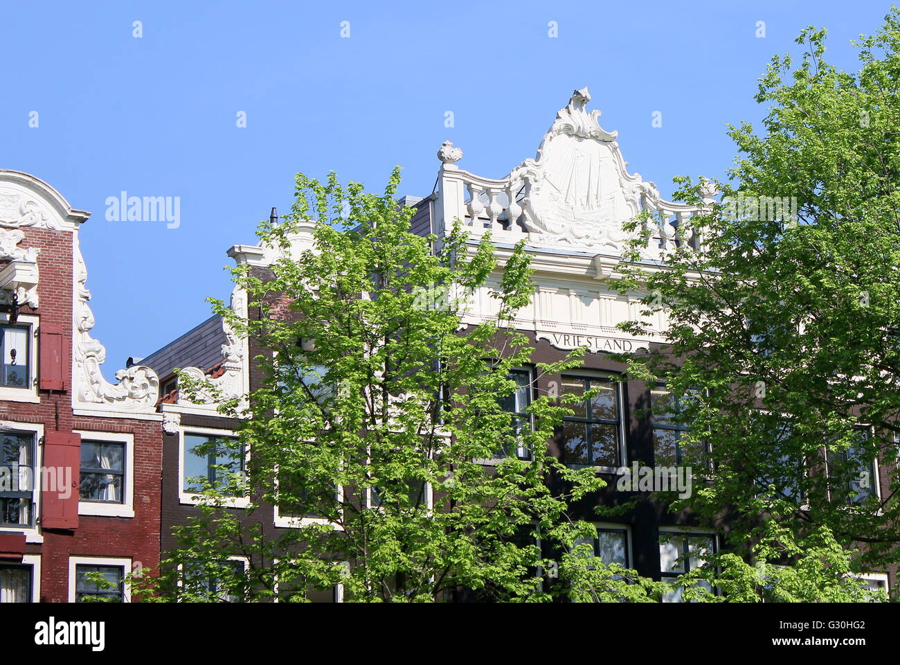 18th century monumental house Vriesland, Prinsengracht canal, Amsterdam, Netherlands. Upper gable decoration with - Stock Image