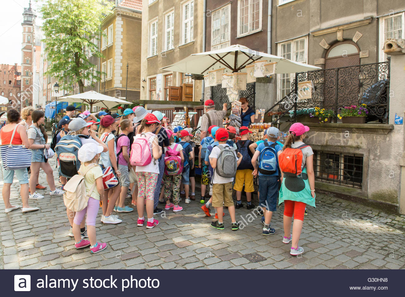 Mariacka Street, Gdansk, Poland - school group listening to teacher or guide explaining about items for sale on - Stock Image