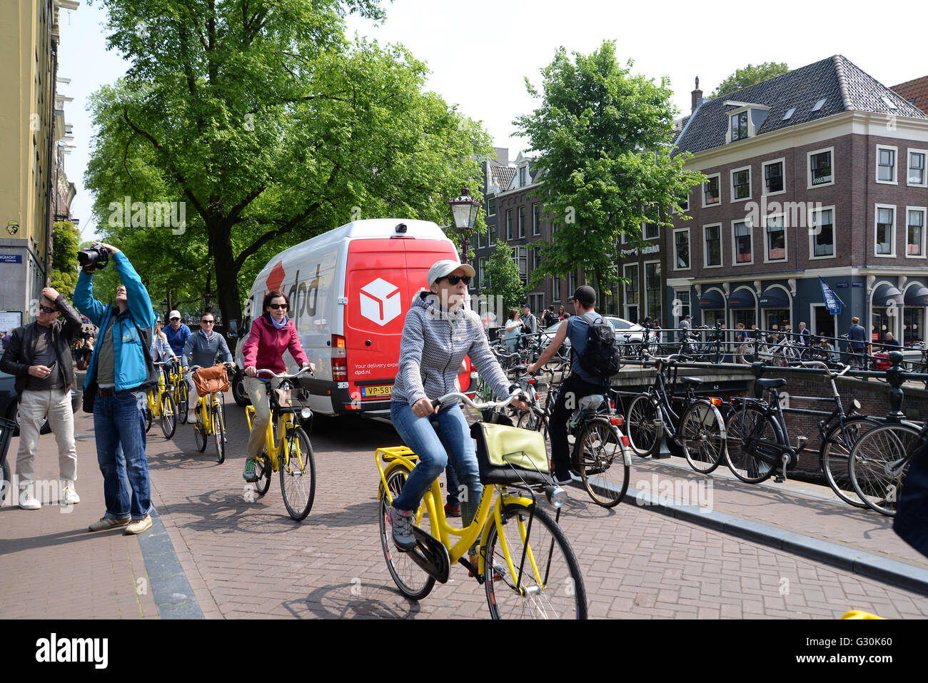 Cyclists in Bike City Amsterdam ride along canal road on bright yellow rented bikes. - Stock Image