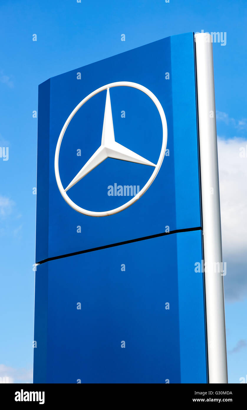 Official dealership sign of Mercedes-Benz over blue sky. Stock Photo