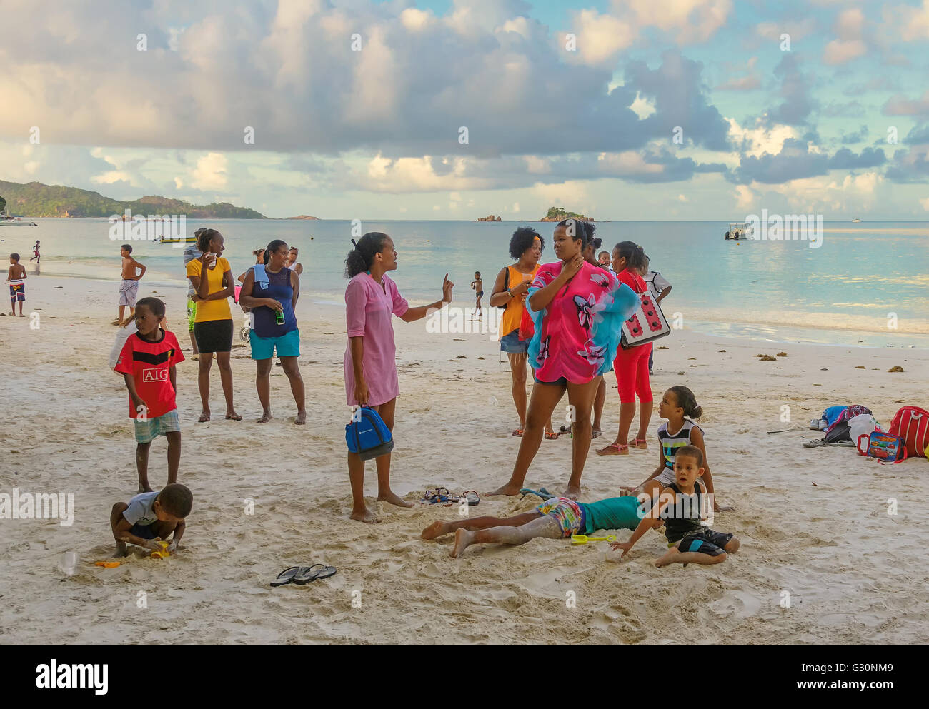 Local people relax in the evening at weekend on the Praslin island beach, Seychelles - Stock Image