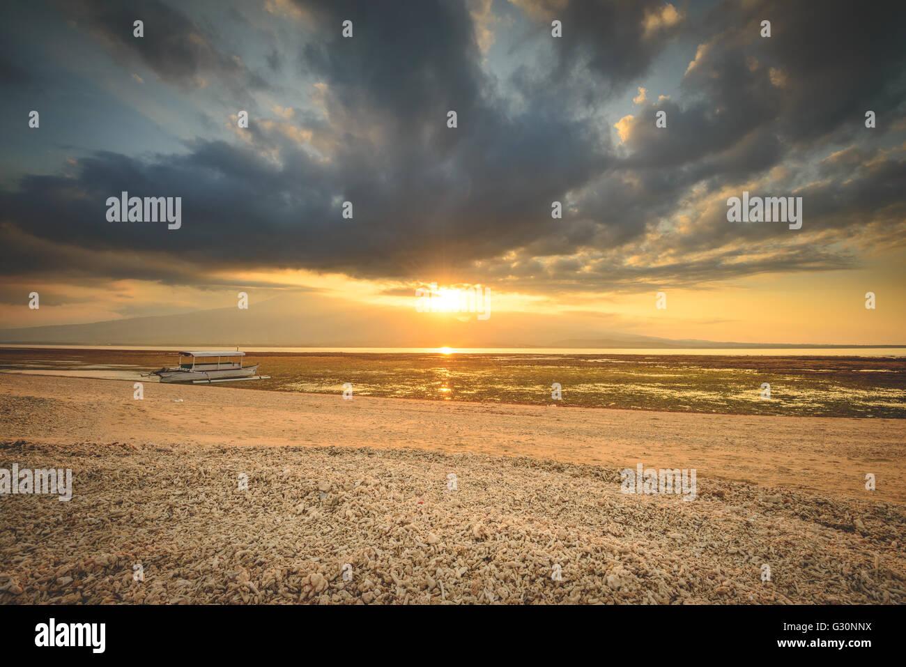 Watching the sun set over Lombok on Gili Lampu Island - Stock Image
