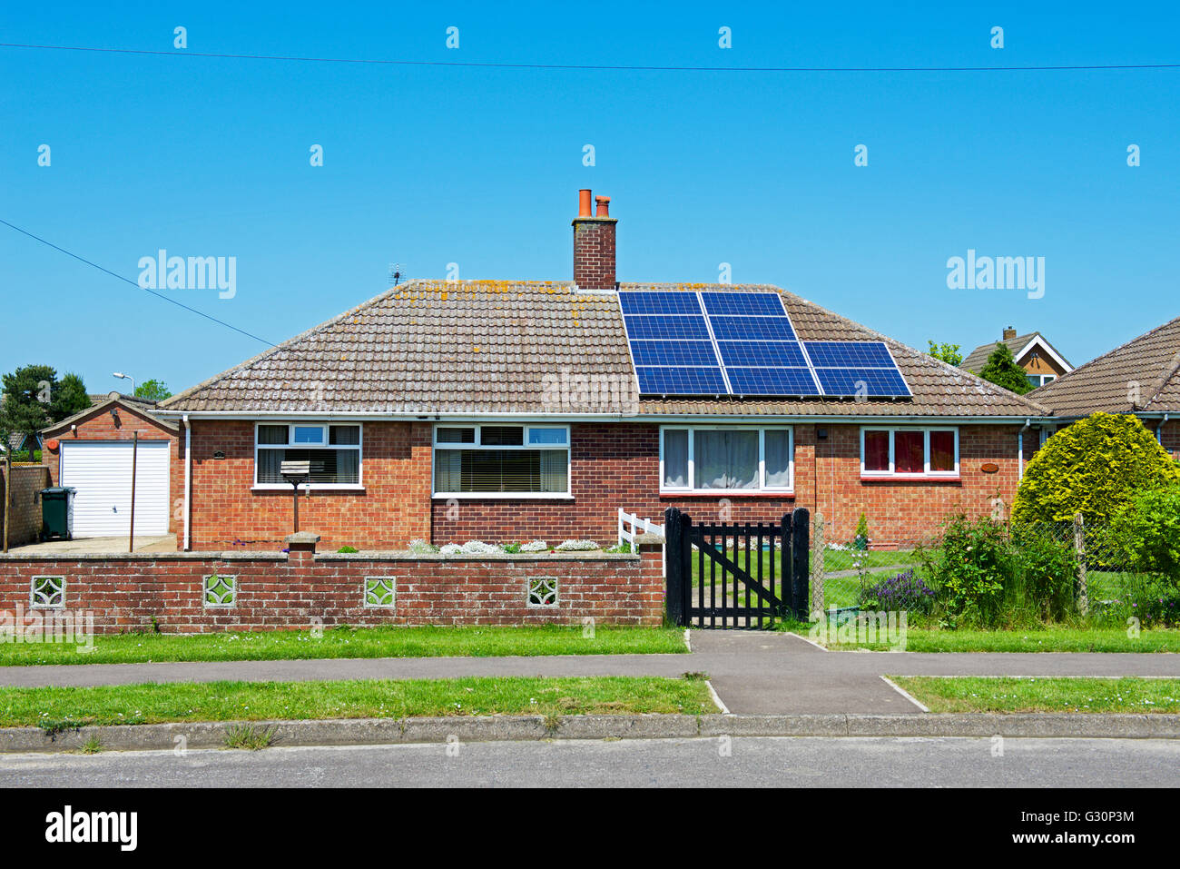 Semi-detached bungalow, half the roof with solar panels, half without, England UK - Stock Image