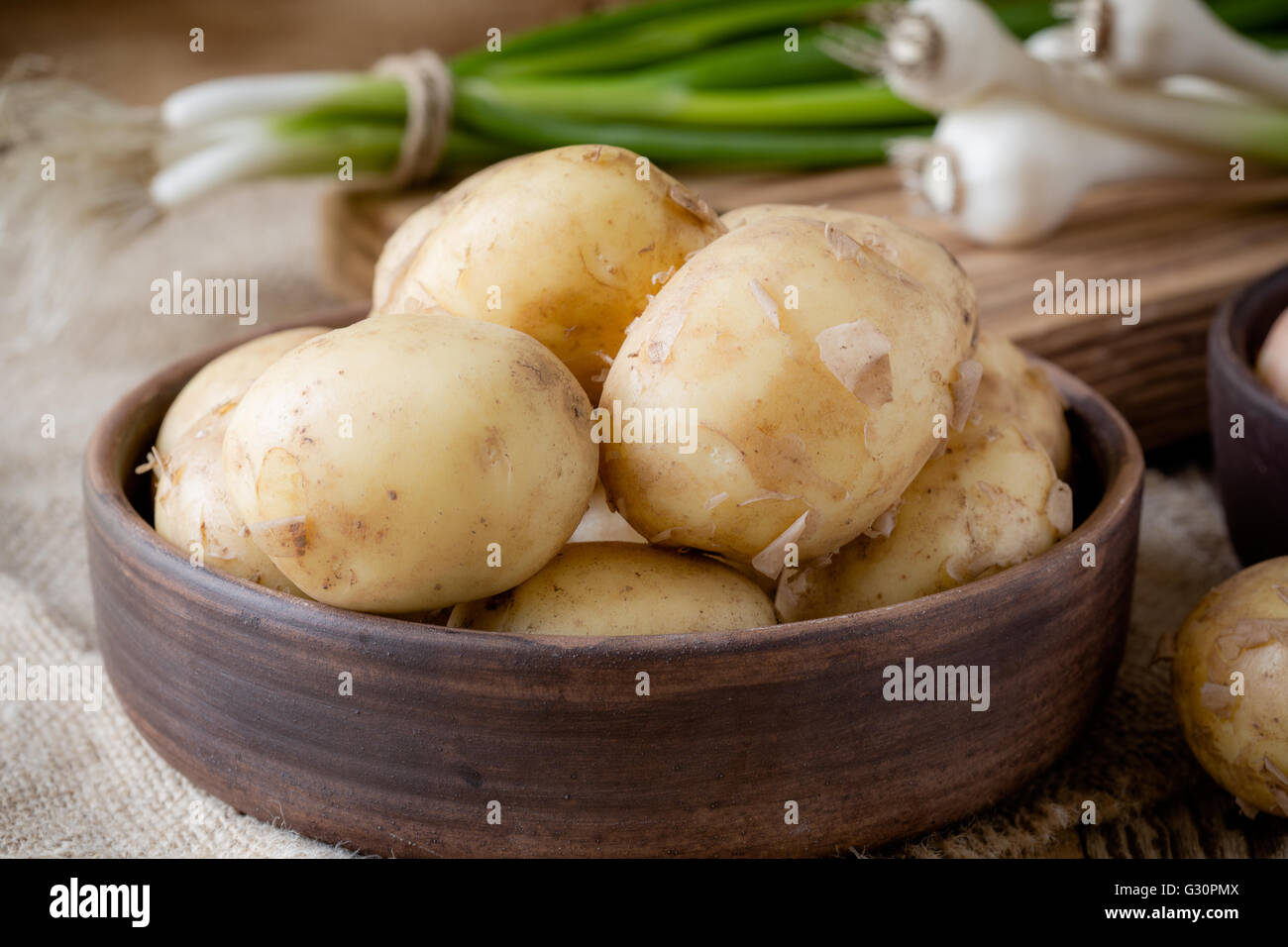 Raw organic potatoes and spring green onion.  Yellow potatoes on rustic wooden table - Stock Image