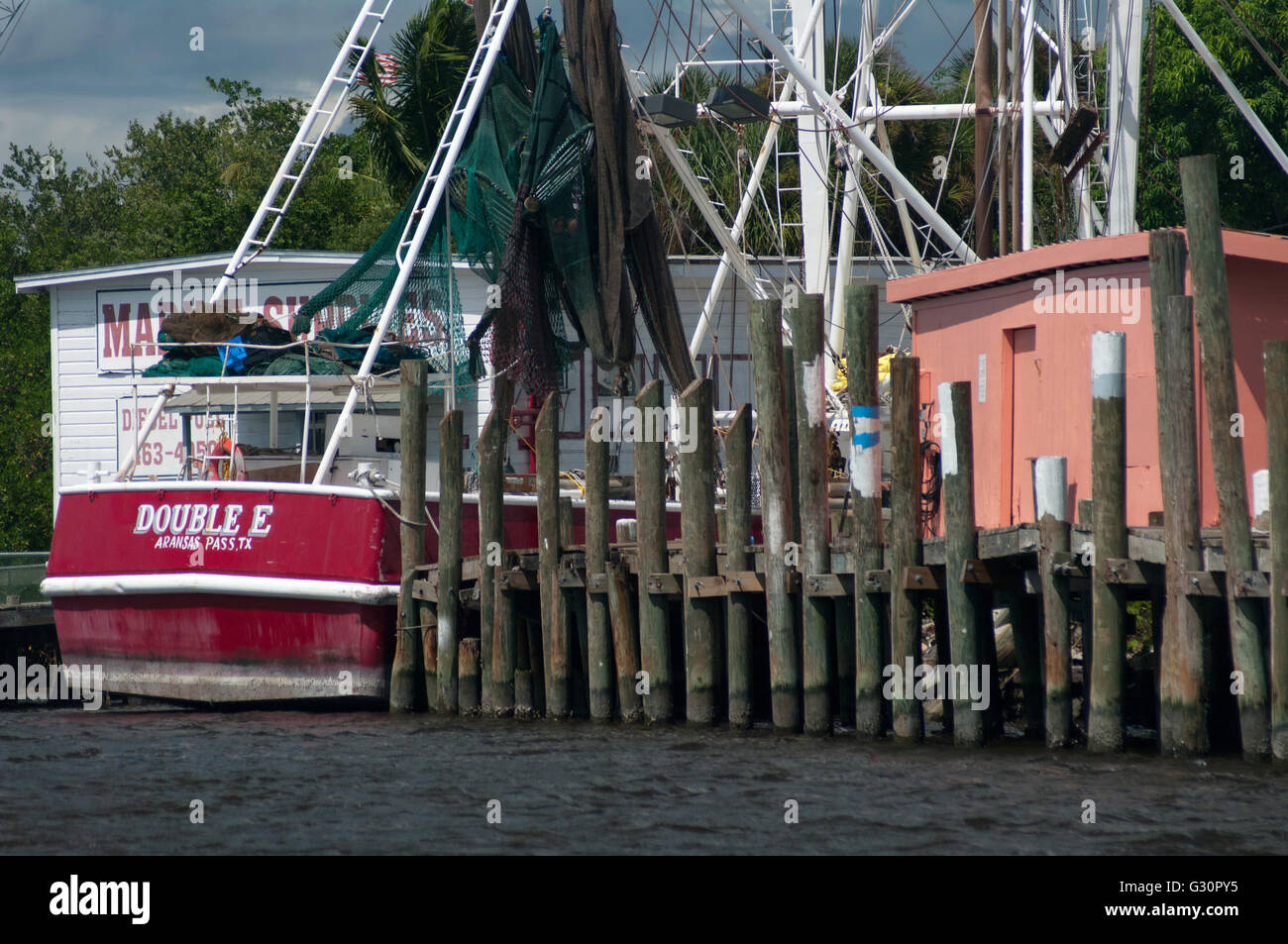 A commercial fishing vessel is moored near a rustic dock in a marina in Fort Myers Beach, Florida, USA. - Stock Image