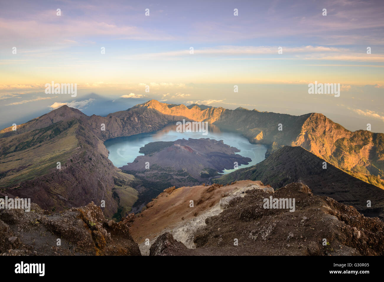 The Mt. Rinjani crater and a shadow cast from the peak at sunrise - Stock Image
