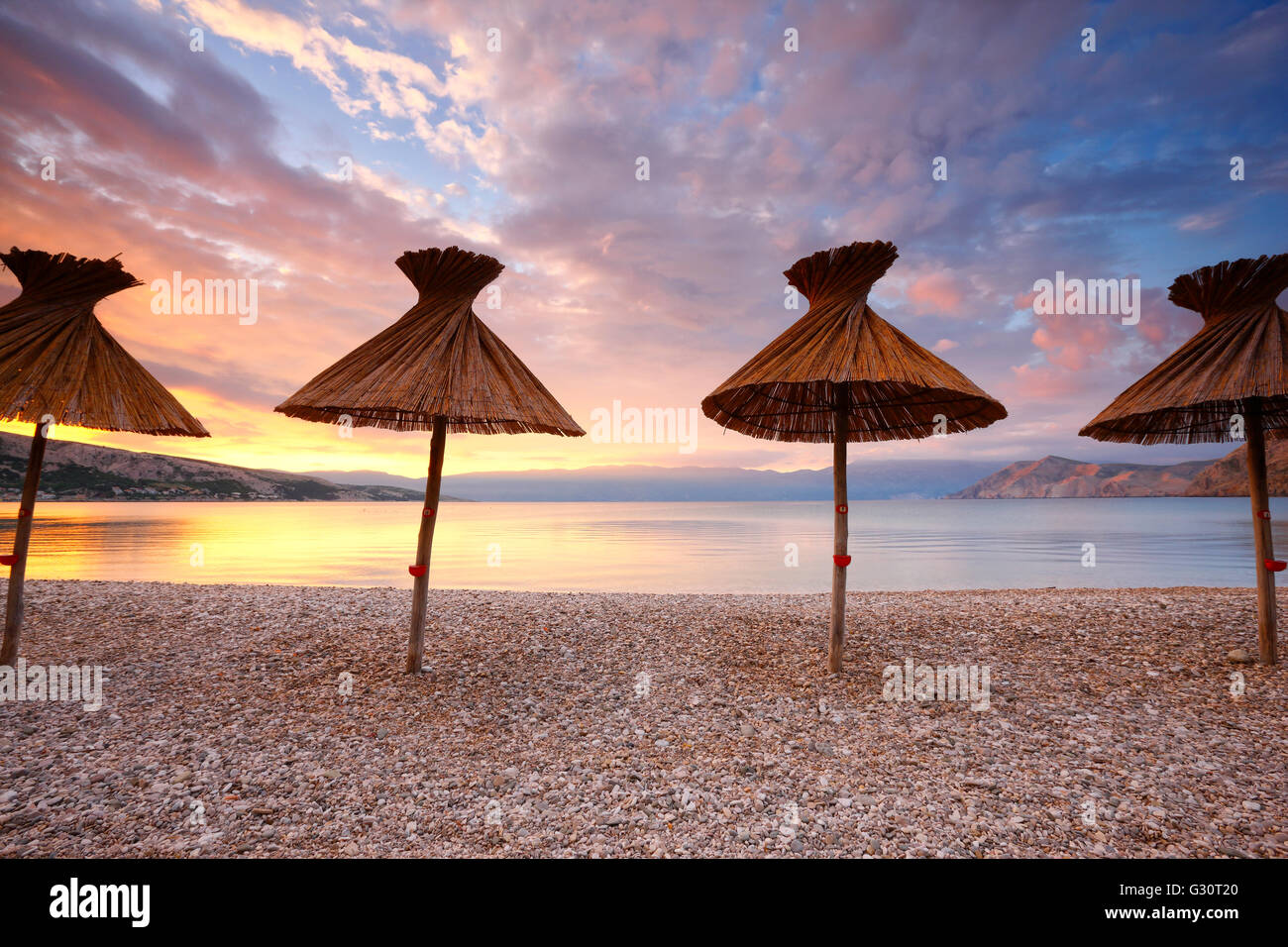 Straw umbrellas on the beach in Baska on island Krk - Stock Image