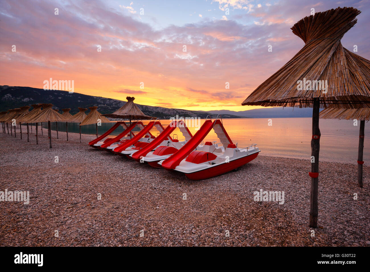 Straw umbrellas and water pedal boats on the beach in Baska, island Krk Stock Photo