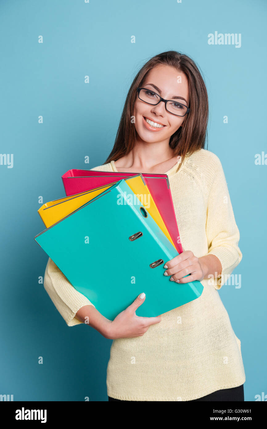 Smiling young girl holding folders isolated on the blue background - Stock Image