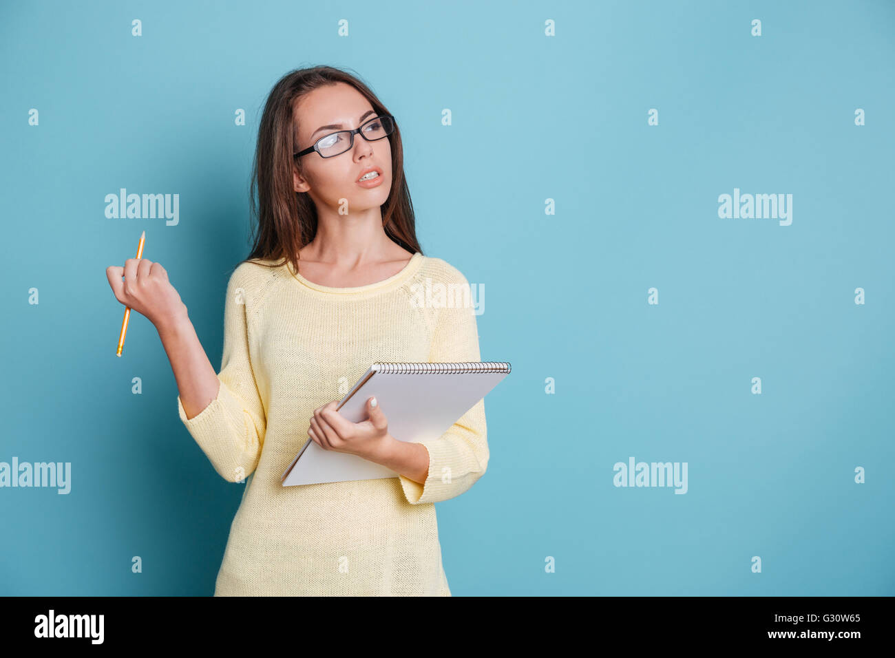 Young smart pensive girl thinking about something and holding colorful binders isolated on the blue background - Stock Image