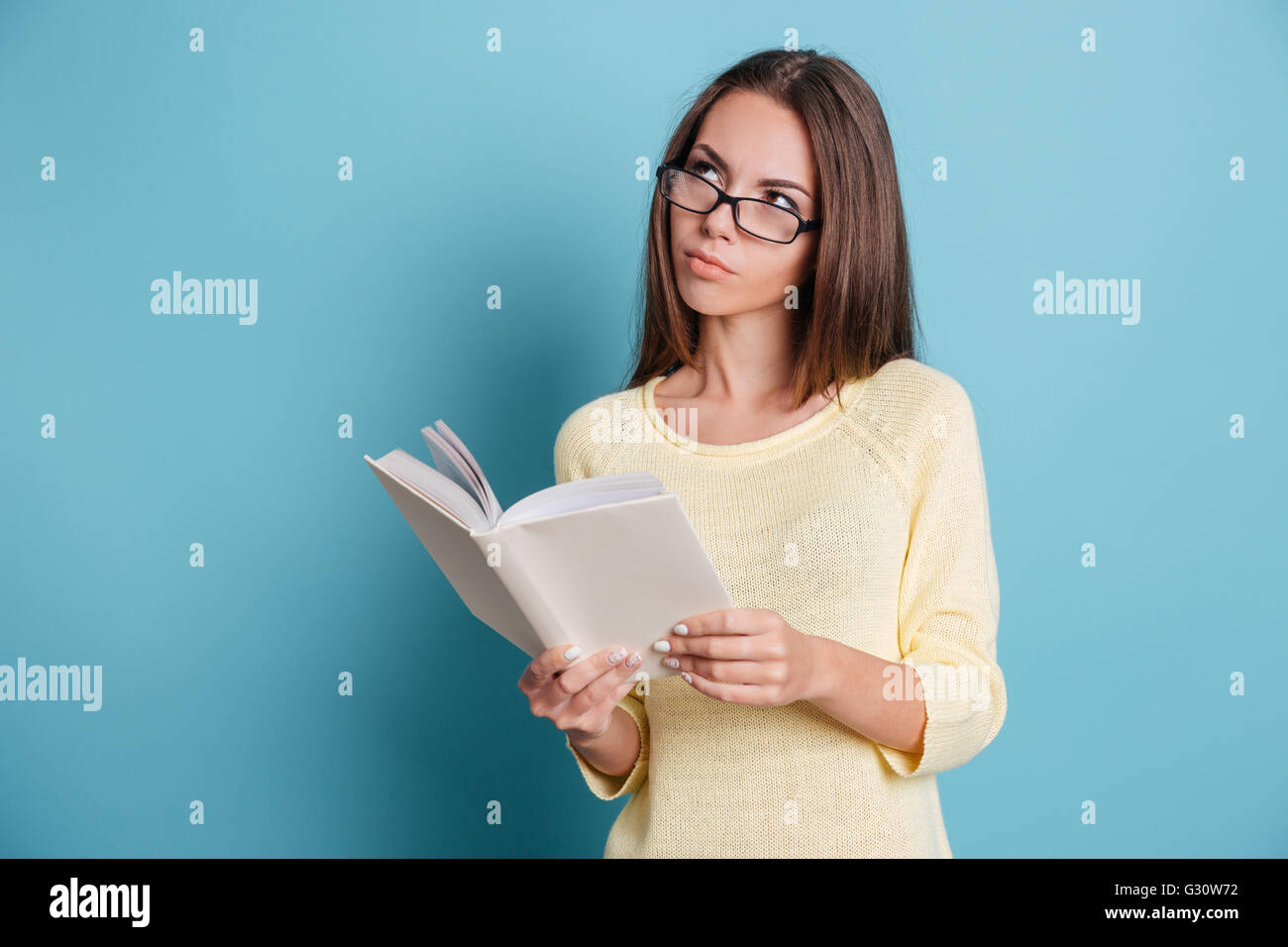 Pensive smart girl thinking about something and holding book isolated on the blue background - Stock Image