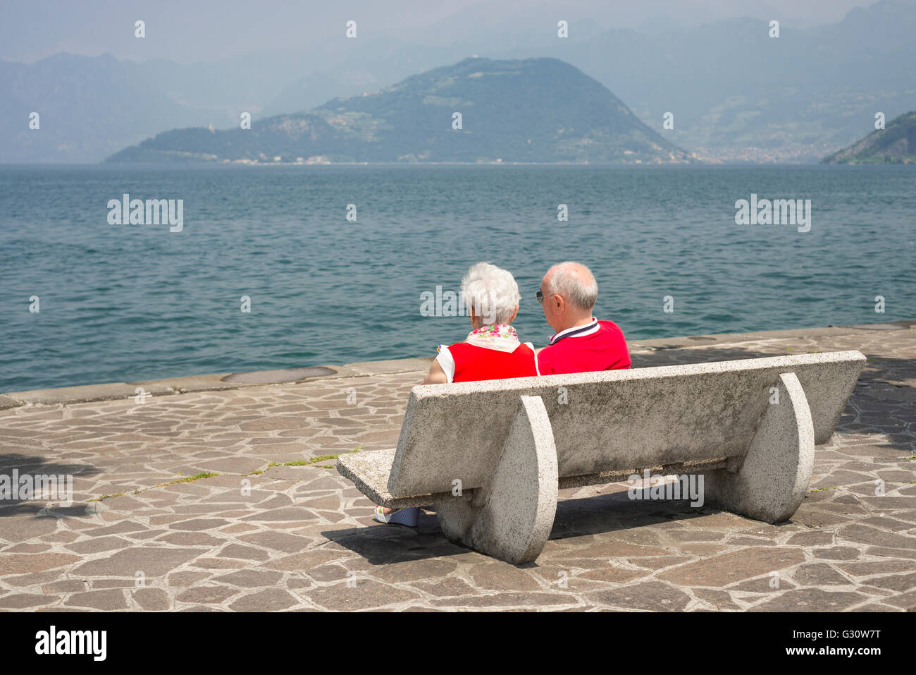 Elderly couple sitting  in the sun on park bench in Iseo on the shore of Lake Iseo, Lombardy, Italy - Stock Image