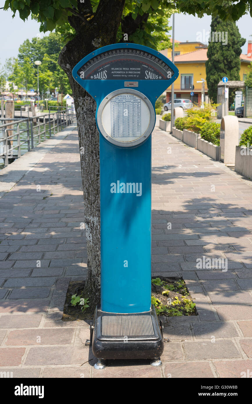 Blue weighing scale under trees on the sidewalk of the lakeside boulevard in Iseo on Lake Iseo, Lombardy, Italy - Stock Image
