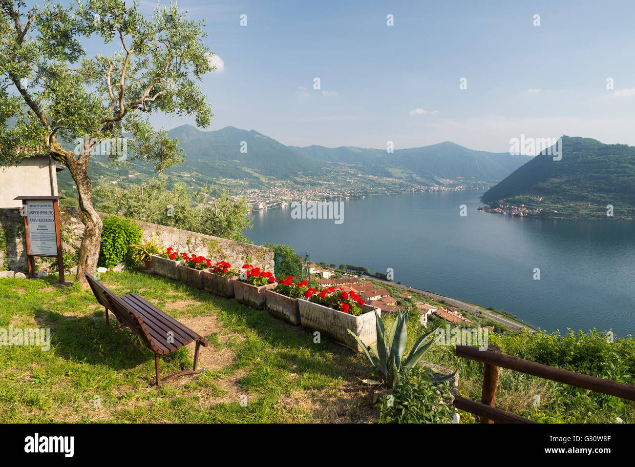 Empty bench at Saint Peter Church in Marone overlooking the panorama of Lake Iseo and Monte Isola island in afternoon - Stock Image