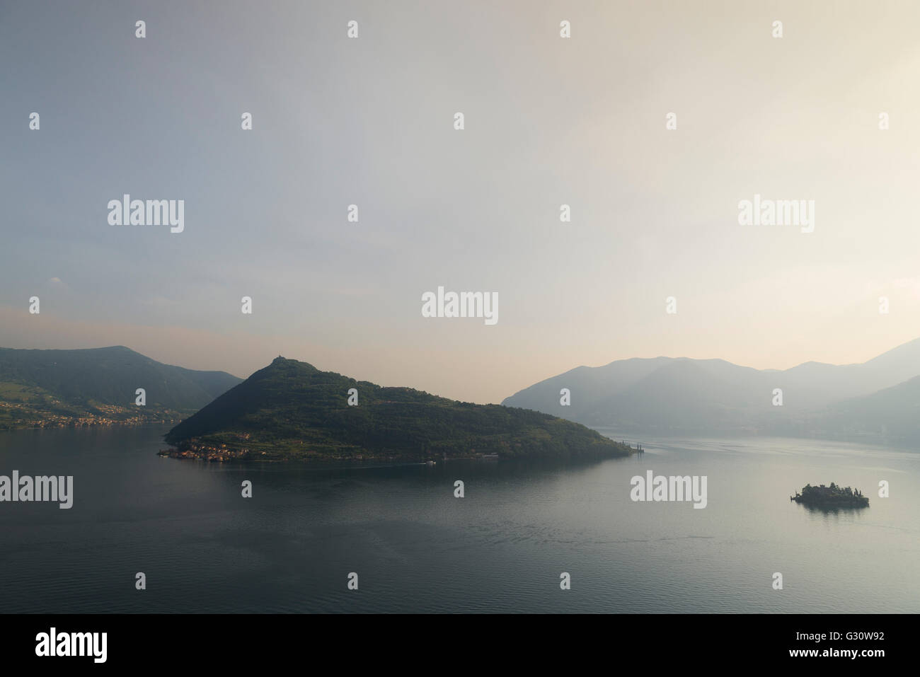 The islands of Monte Isola and Isola di Loreto at Lake Iseo with surrounding mountains and a glowing sky at sunset Stock Photo