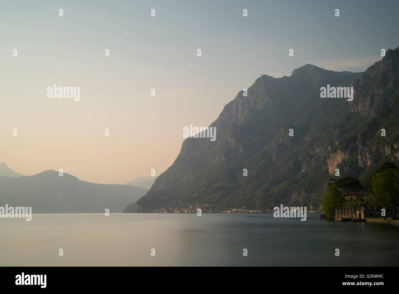 Steep and rugged mountain cliffs and rocks at the lakeside near Marone at Lake Iseo in warm sunlight at sunset, - Stock Image
