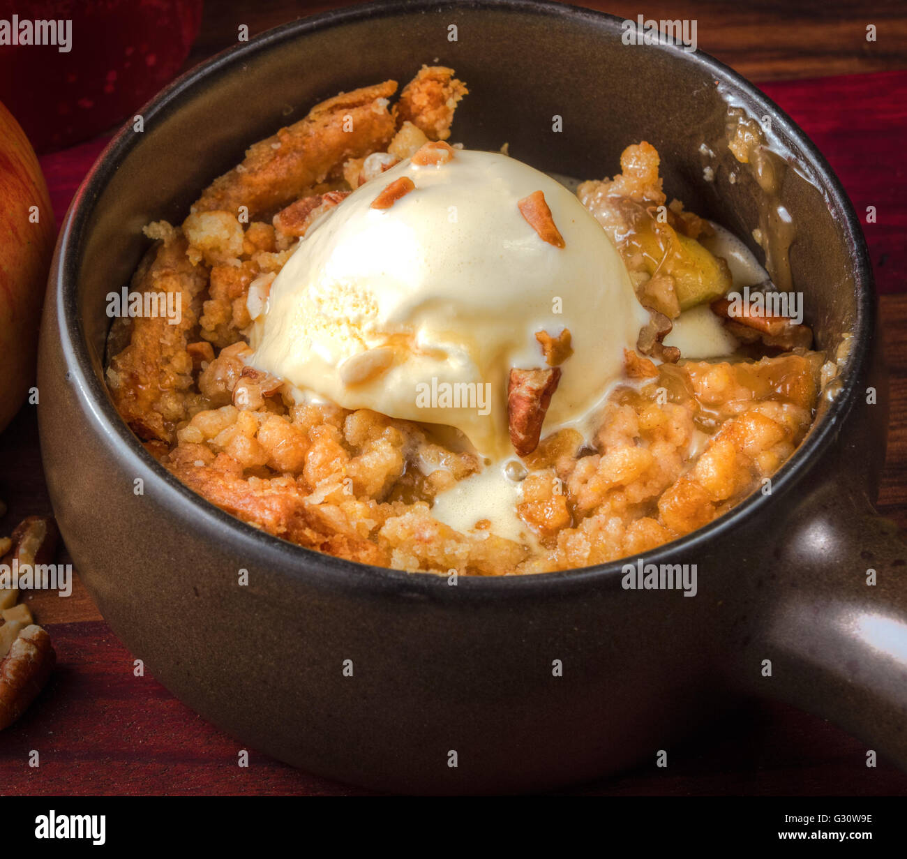 Apple Crisp A La Mode. Fresh hot apple crisp with a scoop of ice cream and homemade caramel sauce. - Stock Image