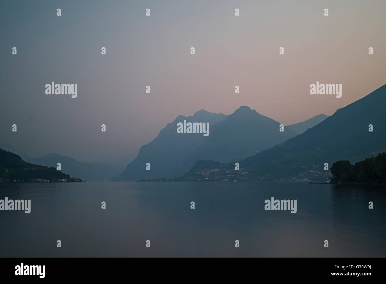 Tranquility over alpine mountains and villages and Lake Iseo at dawn in spring,Lombardy,Italy - Stock Image