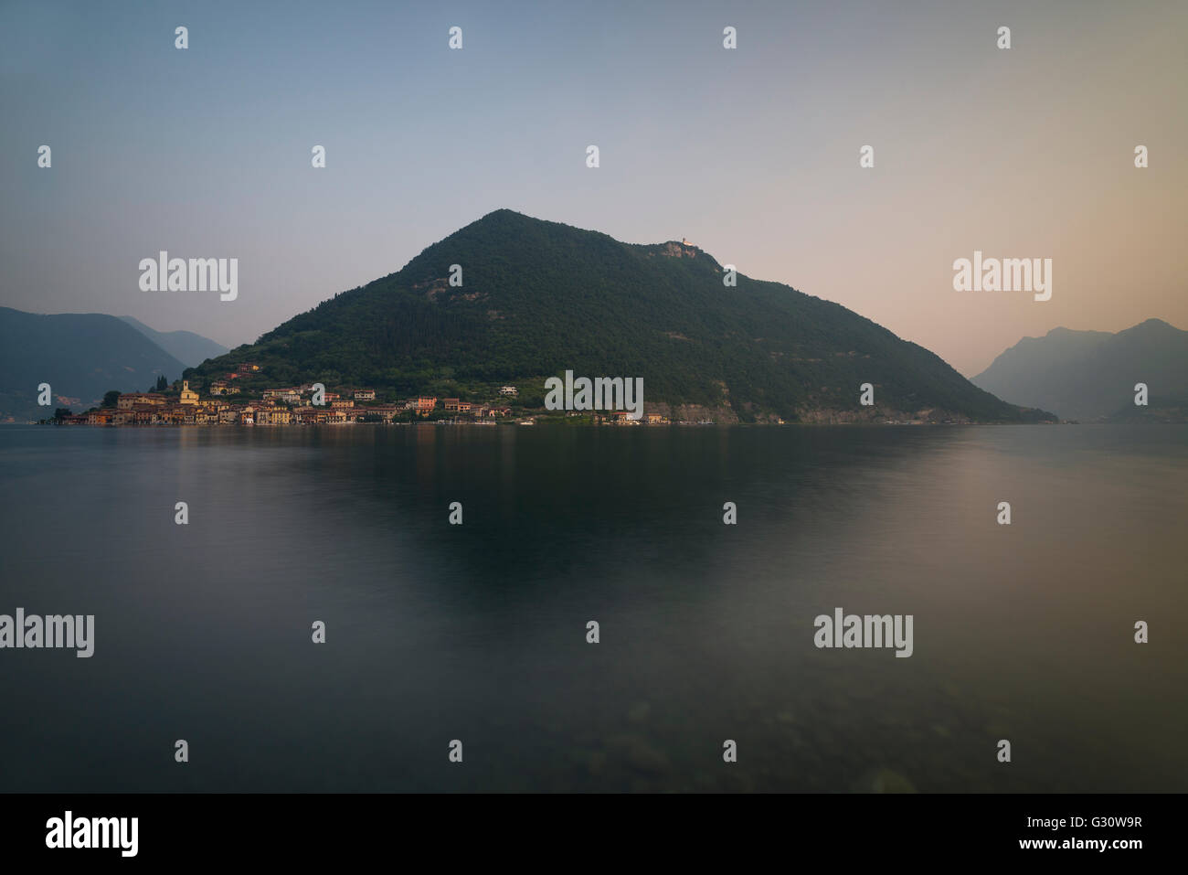 Panorama of scenery with Monte Isola island at Lake Iseo at dawn shortly before sunrise,Sulzano,Lombardy,Italy - Stock Image