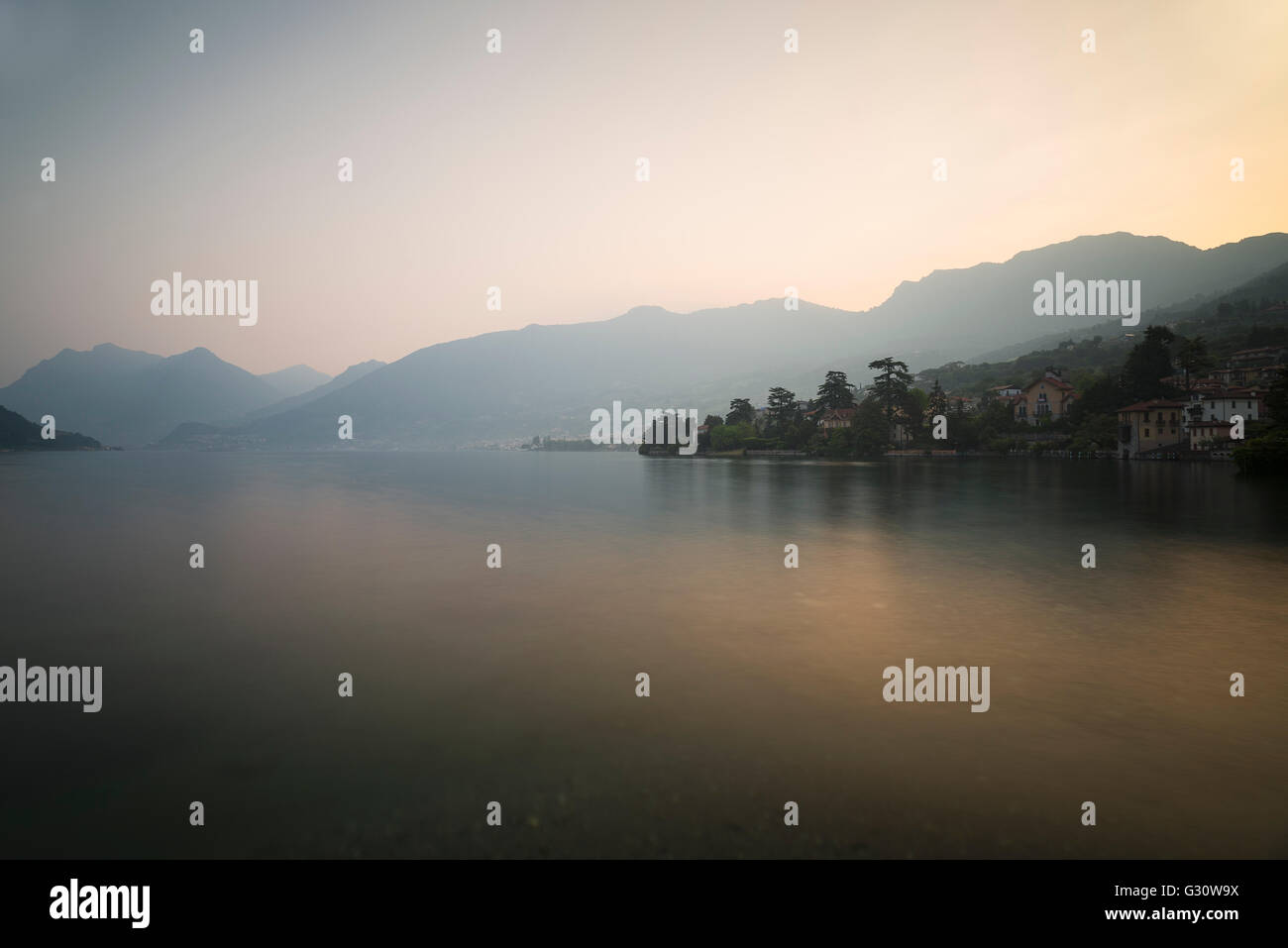 Panorama of scenery with mountains and villages at Lake Iseo at dawn shortly before golden sunrise,Sulzano,Lombardy,Italy - Stock Image