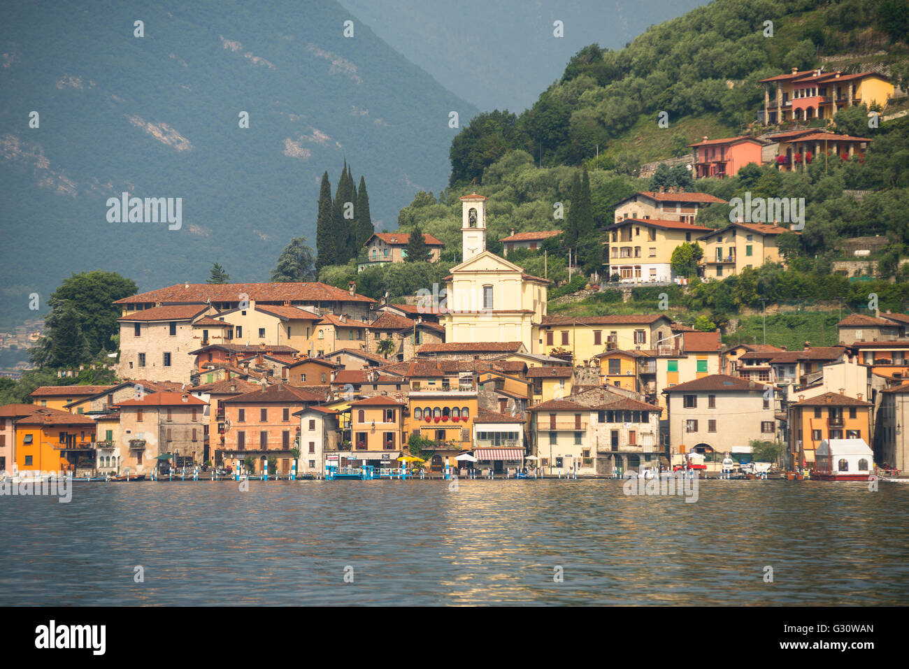 Colorful houses of Peschiera Maraglio on wooded mountain slopes on the shores of the island Monte Isola on Lake - Stock Image