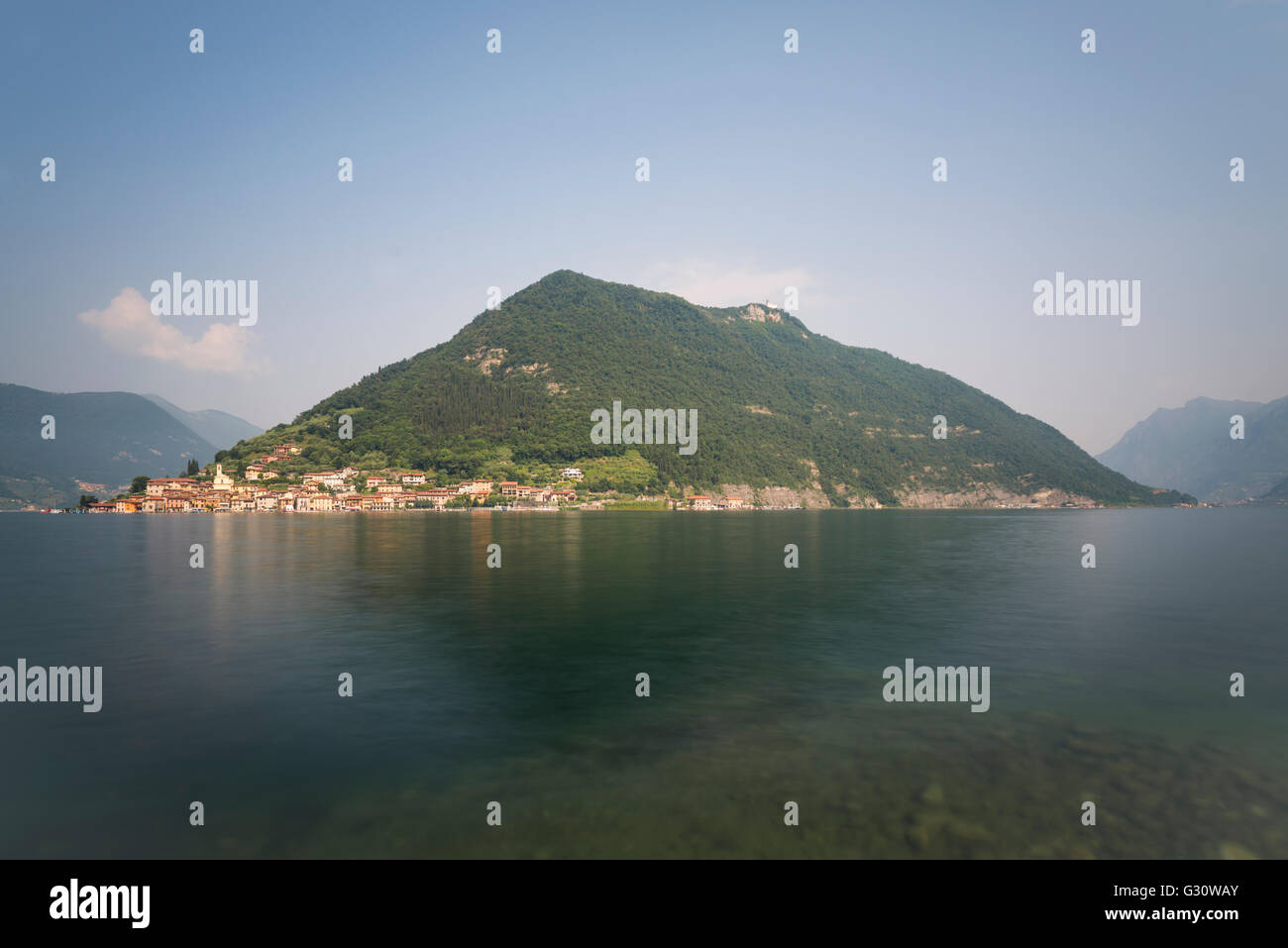 Panorama with Peschiera Maraglio village at the slopes of Monte Isola island at Lake Iseo at sunrise,Sulzano,Lombardy,Italy - Stock Image