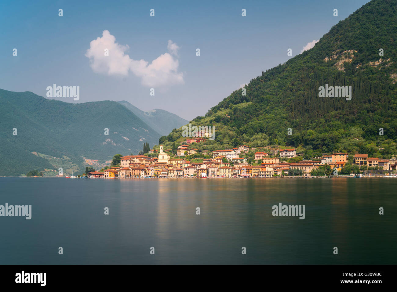 Colorful houses of Peschiera Maraglio on wooded mountain slopes on the shores of the island Monte Isola in Lake - Stock Image