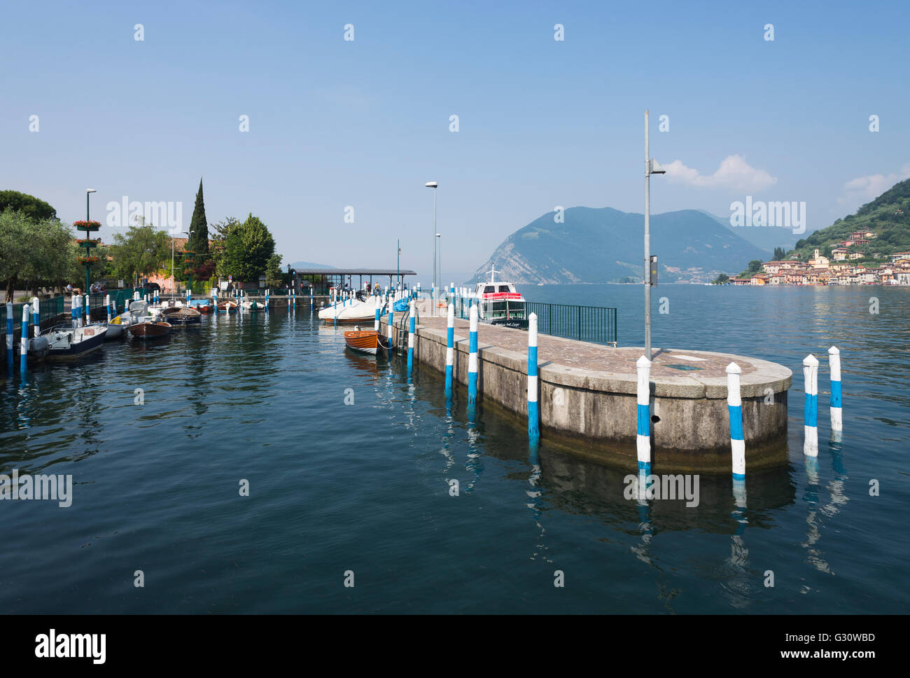 Colorful poles at the port of Sulzano on Lake Iseo with the panorama of Monte Isola and the rocky coast, Lombardy, - Stock Image