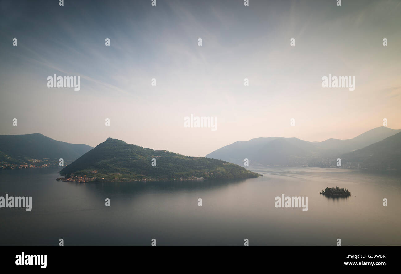 The islands of Monte Isola and Isola di Loreto at Lake Iseo with surrounding mountains and glowing sky at sunset,Lombardy,Italy - Stock Image