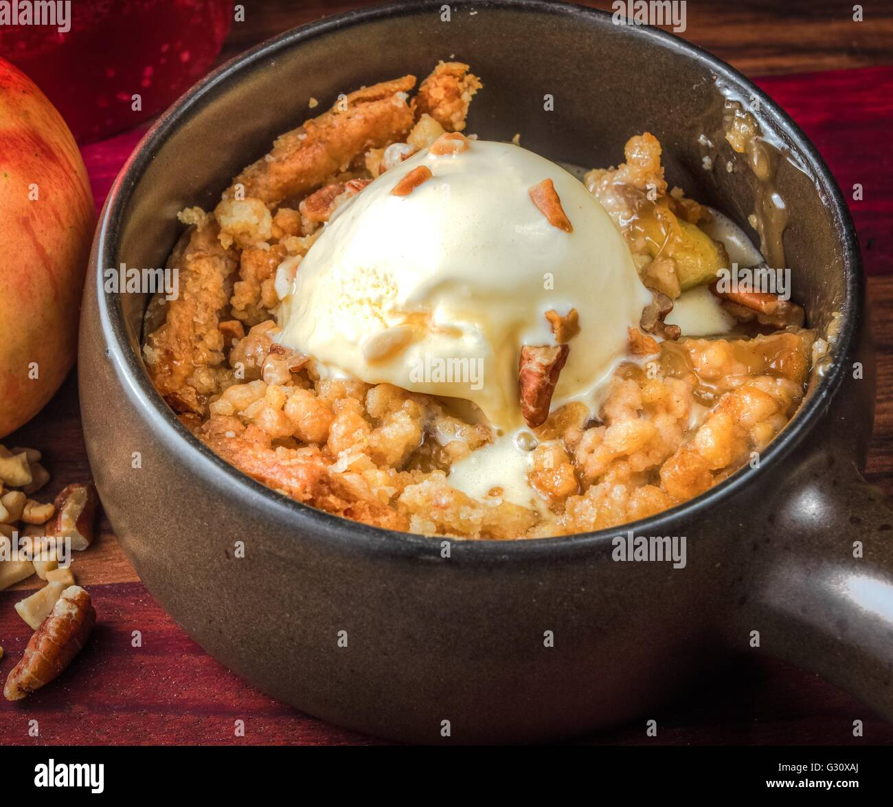 Freshly baked apple crisp a la mode with a walnut topping. A delicious seasonal dessert. - Stock Image
