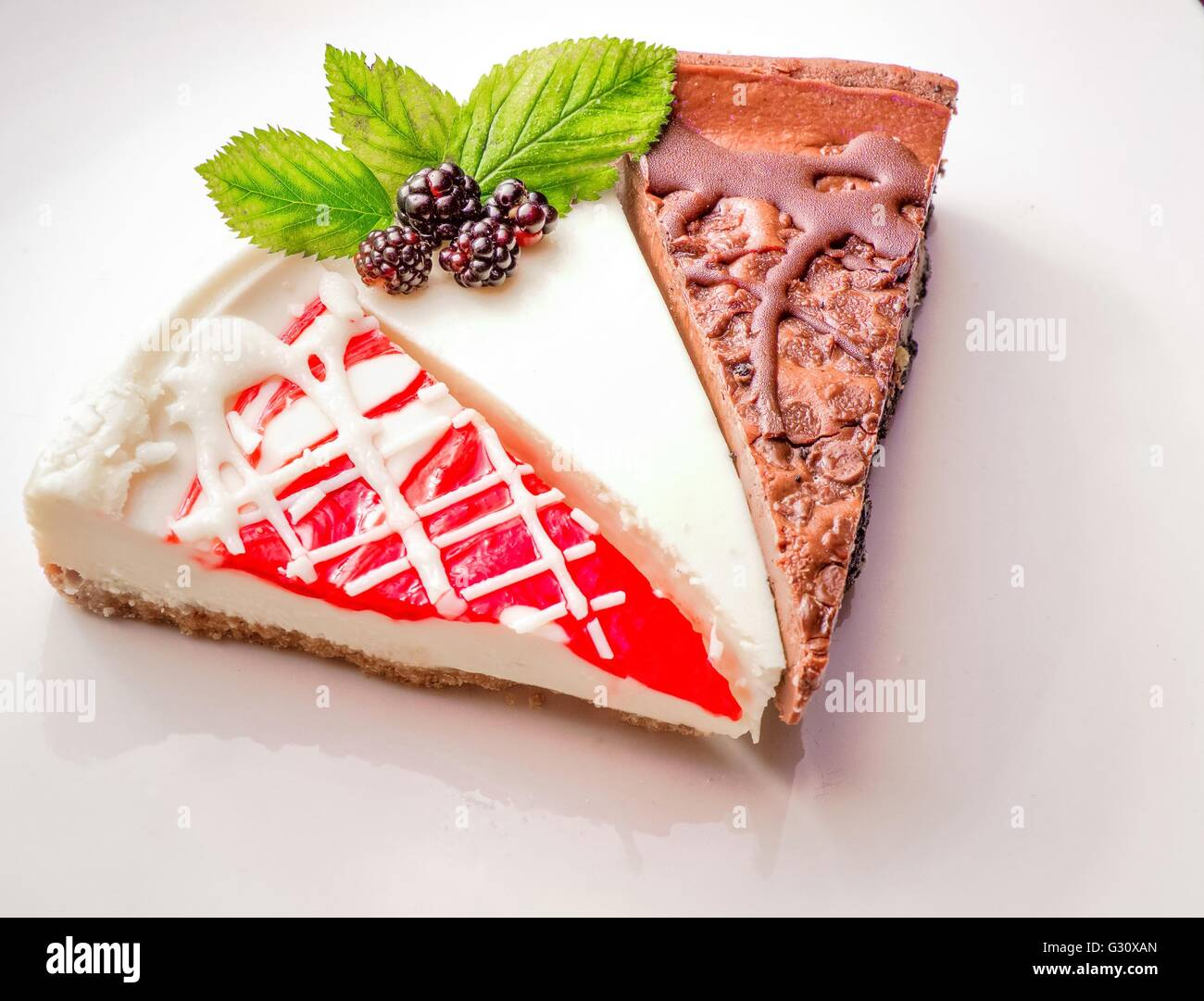 Cheesecake Sampler. Three slices of fresh cheesecake including chocolate, plain and strawberry, - Stock Image