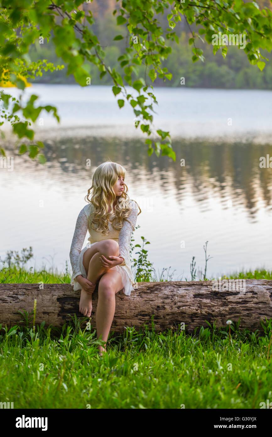 Country-girl on lake river quiet riverside in beige dress mini short minidress curly curls blonde hair sitting on - Stock Image