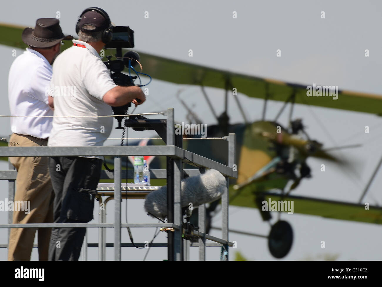 A Polikarpov Po-2 comes in to land passing the video camera and commentator at a Shuttleworth airshow - Stock Image