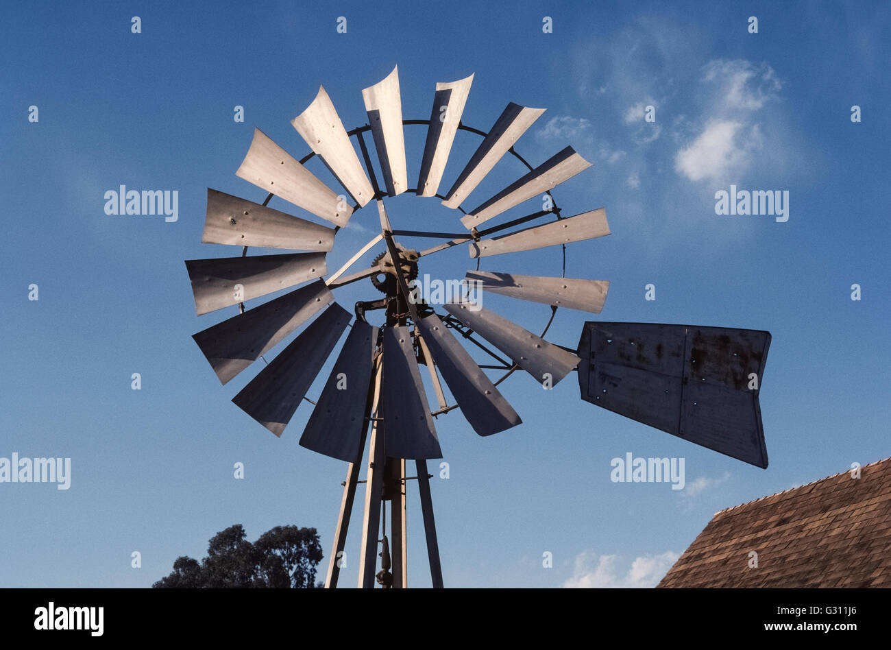 The metal blades and tail vane of a farm windmill that pumps water from the ground are seen close up alongside a - Stock Image