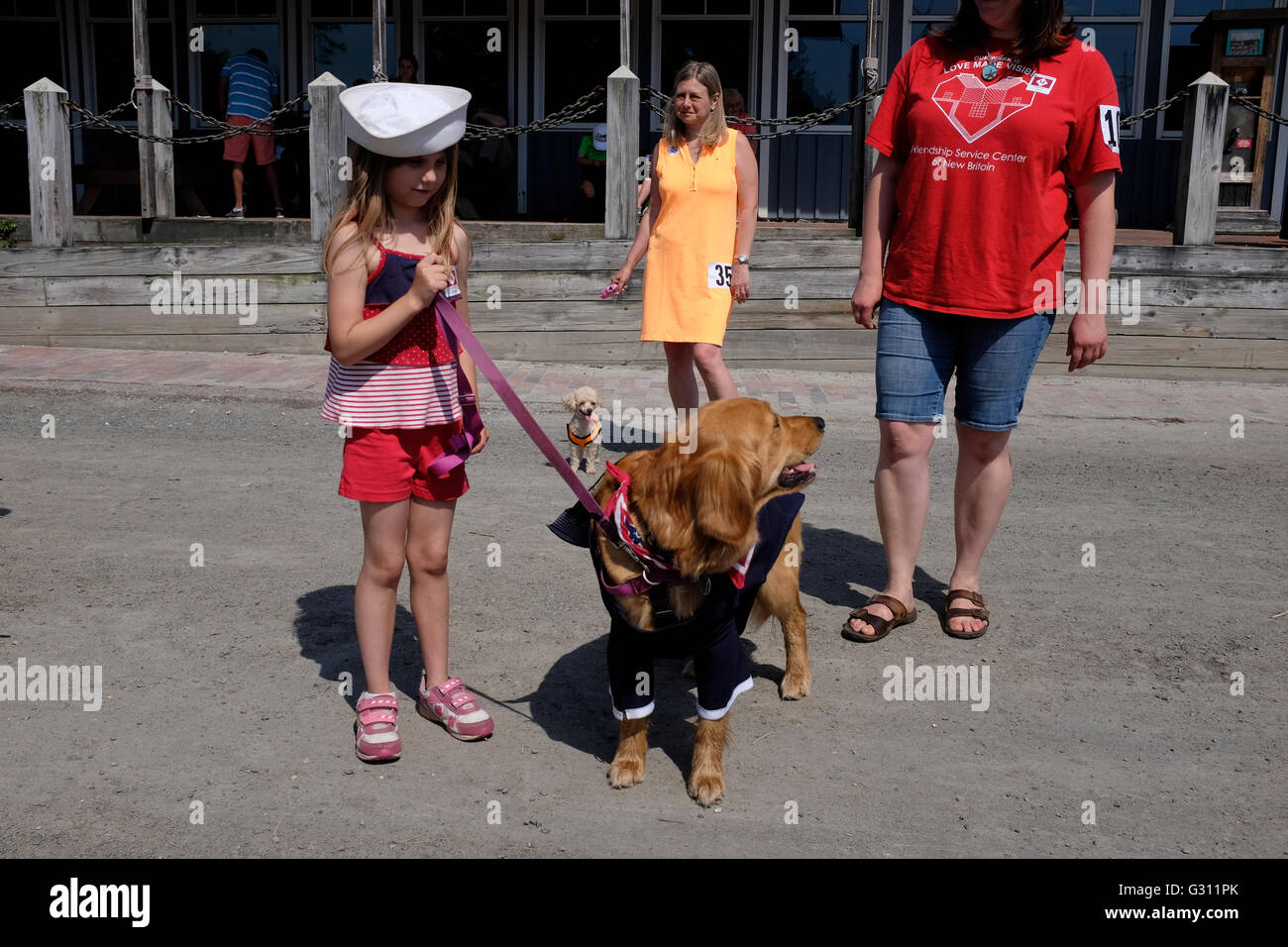 Little girl dressed as a sailor with her dog dressed the same at Costumed Dog Parade in Mystic Seaport, Connecticut - Stock Image