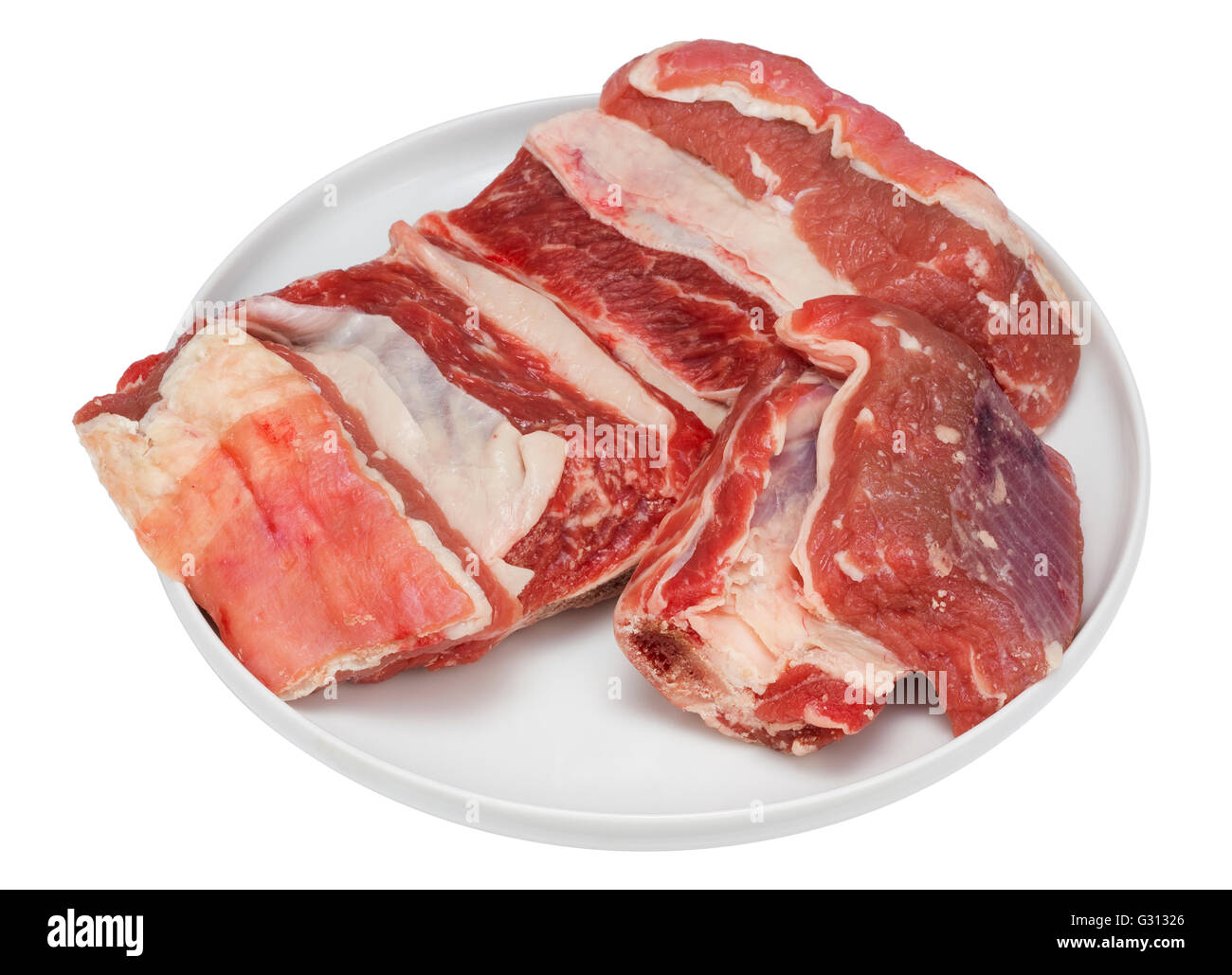 pieces of fresh beef ribs with a bone and fat on the round white ceramic plate cheap ingredient for tasty soup isolated with