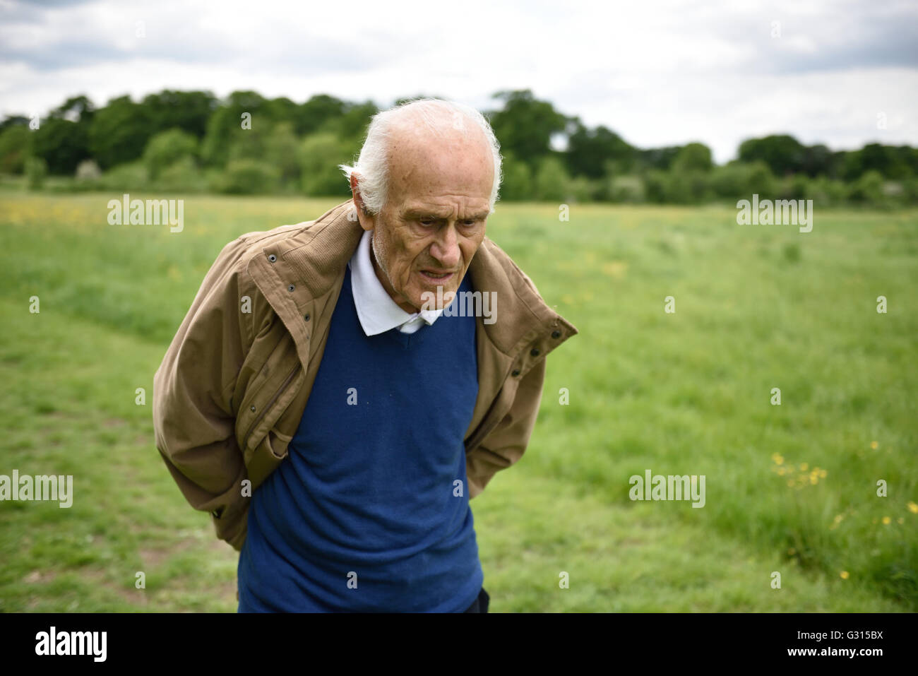An elderly man with dementia looking thoughtful, walking on his own in the countryside looking confused and vulnerable. - Stock Image