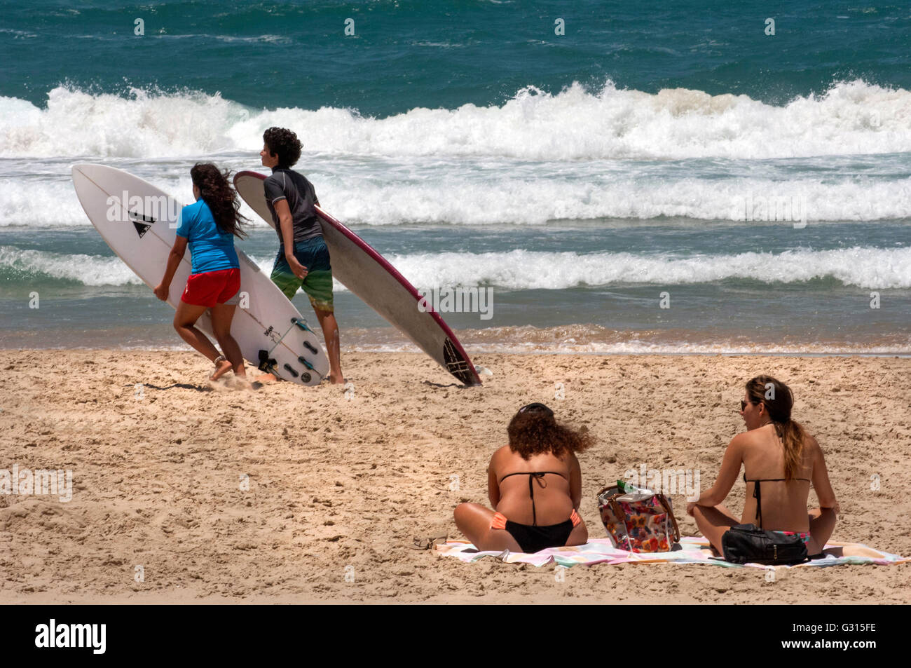 Surfers heading for the waves at the beaches of Tel Aviv, Israel. - Stock Image
