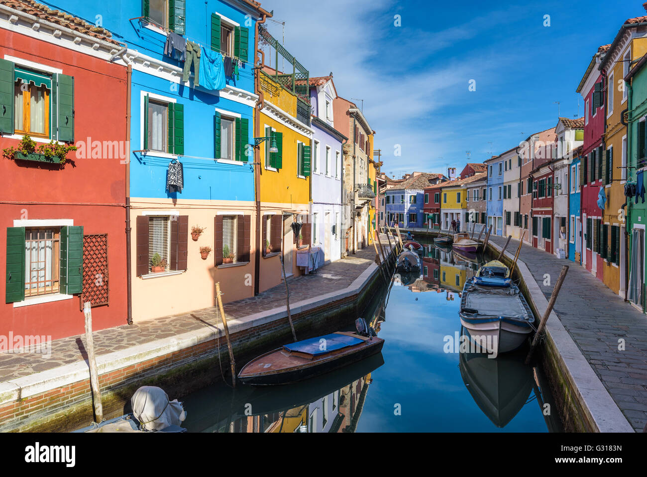 Unusually painted buildings, boats parked in the canals, the town of Burano. - Stock Image