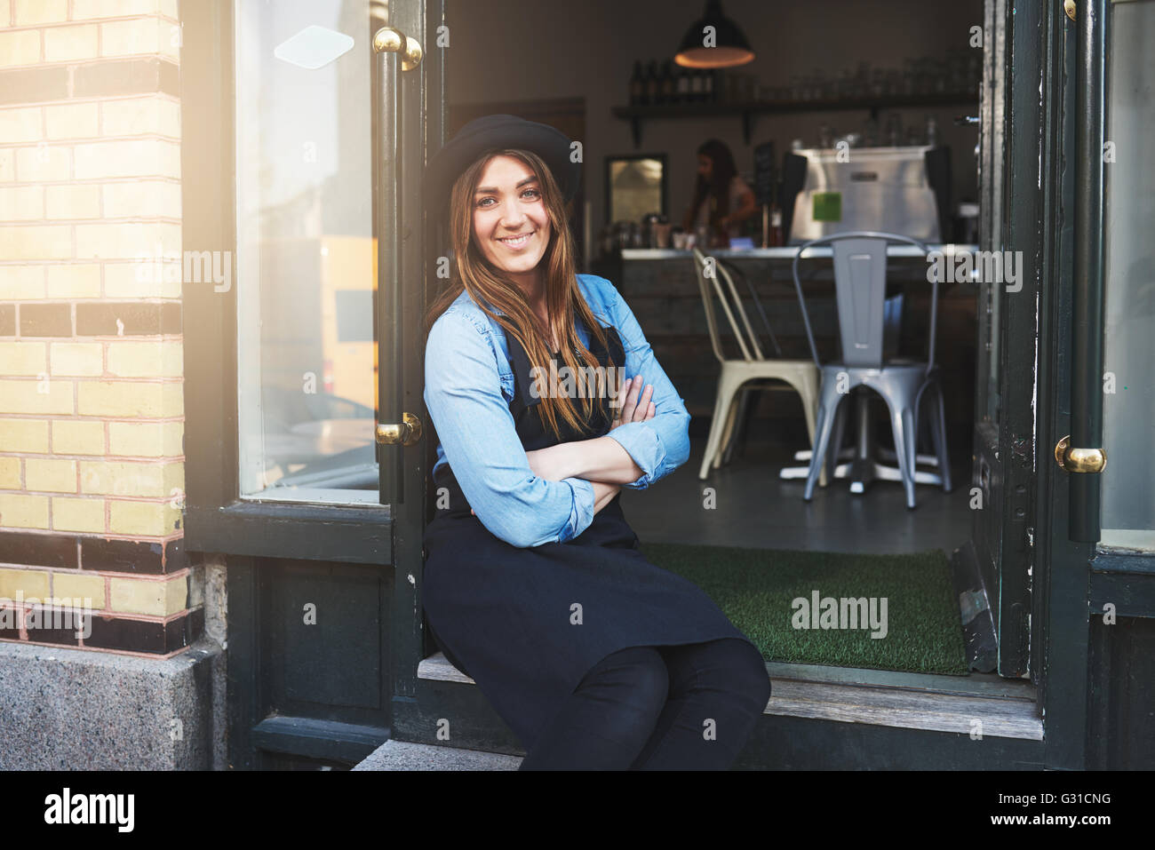 Single cute female coffee house owner in blue shirt, black apron and hat with folded arms sitting in doorway of - Stock Image