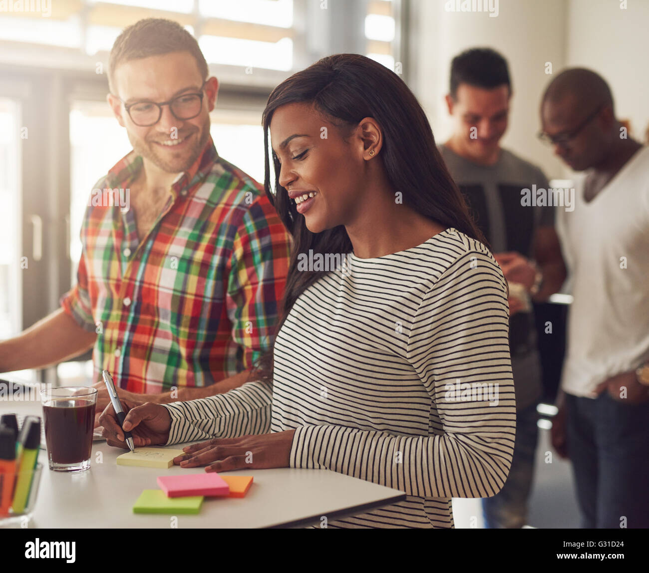 Attractive male wearing eyeglasses and flannel shirt standing next to female co-worker writing on sticky notes at - Stock Image