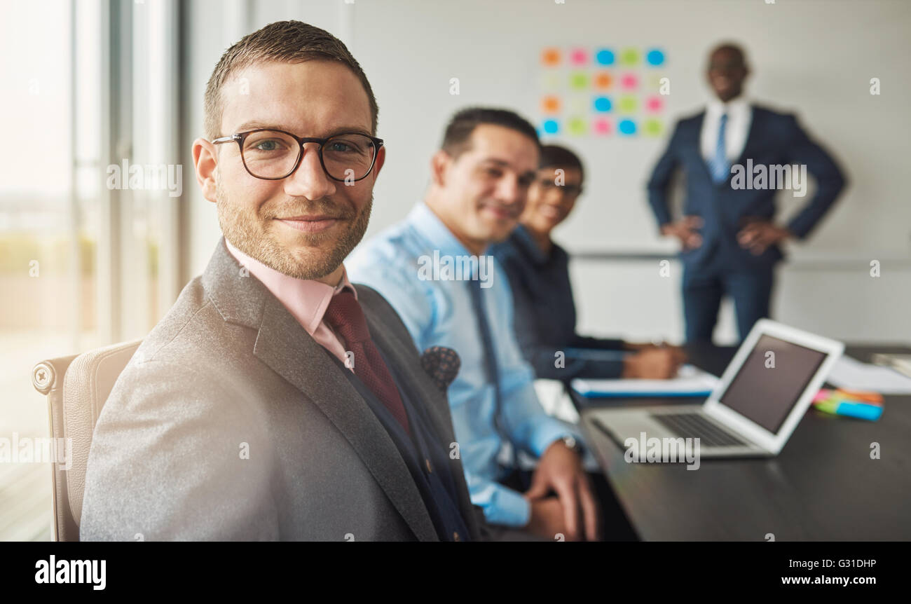 Handsome bearded man wearing suit and tie with three professional co-workers in meeting at conference table in front - Stock Image