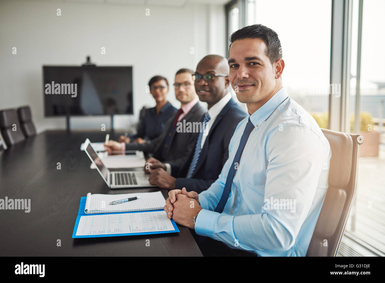 Multiracial executive business team in a meeting seated at a corporate conference table with focus to a Hispanic - Stock Image