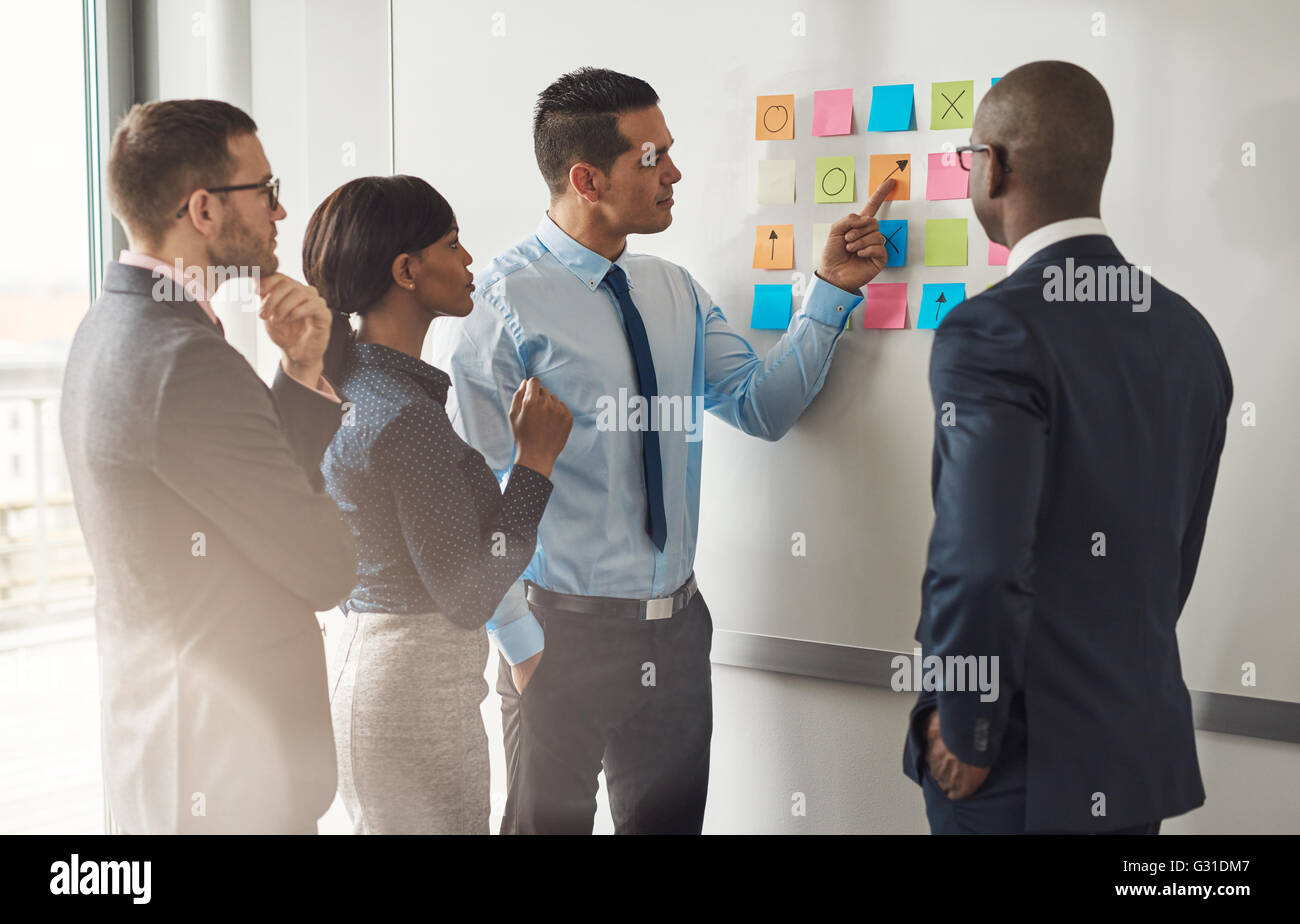 Multiracial group of colleagues discussing a business plan standing around a set of colorful memo notes stuck on - Stock Image