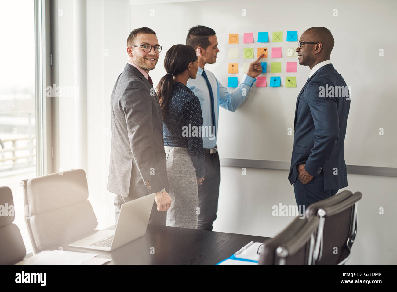 Cheerful group of diverse business people in conference meeting using colorful sticky notes to organize ideas on - Stock Image