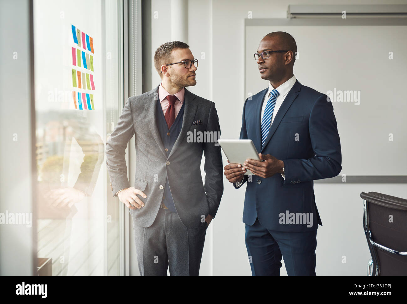 Two smart business managers or office co-workers in a discussion standing in front of a window with colorful memos - Stock Image