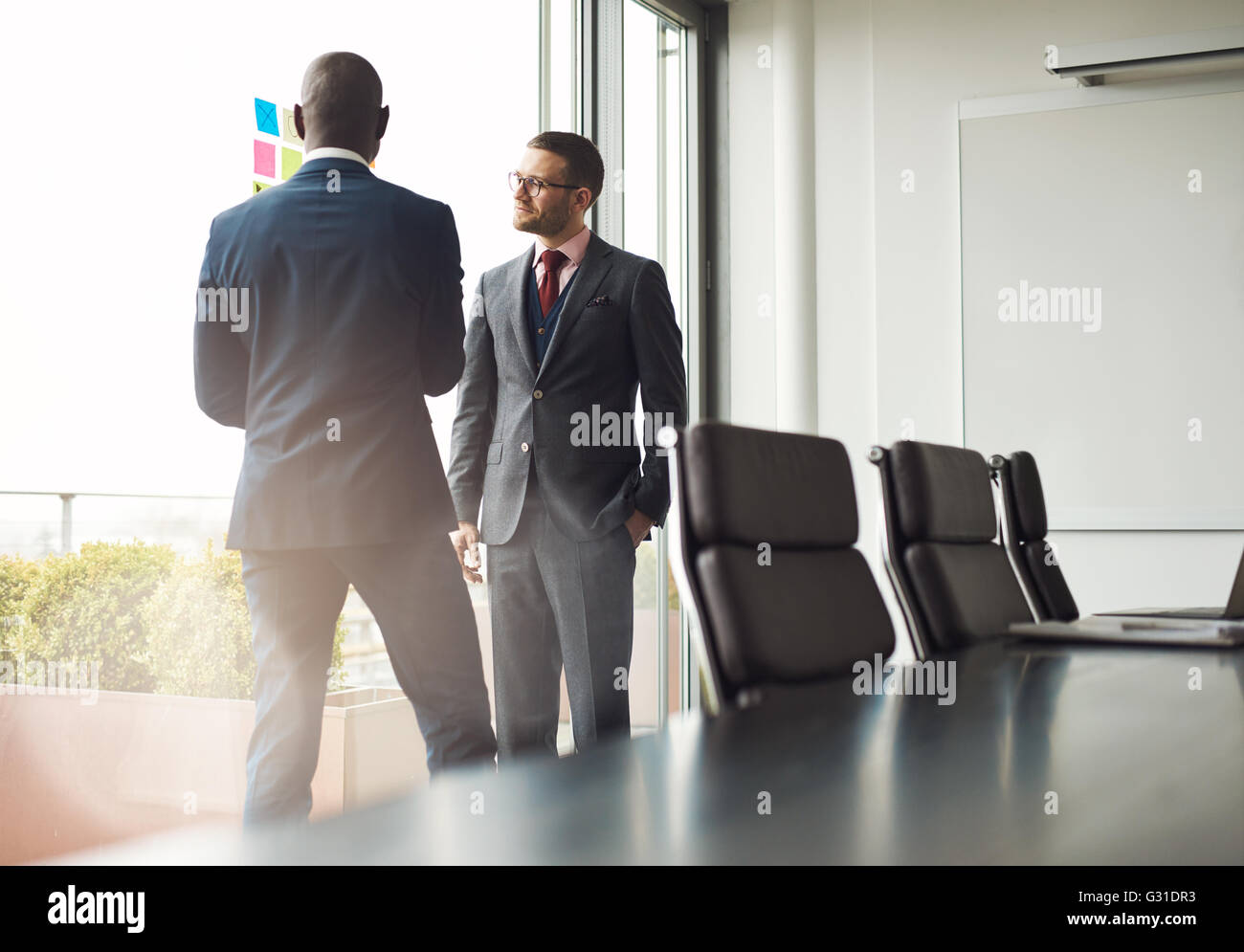 Two multiracial businessmen standing talking together in front of a window in a conference room, view over the table - Stock Image