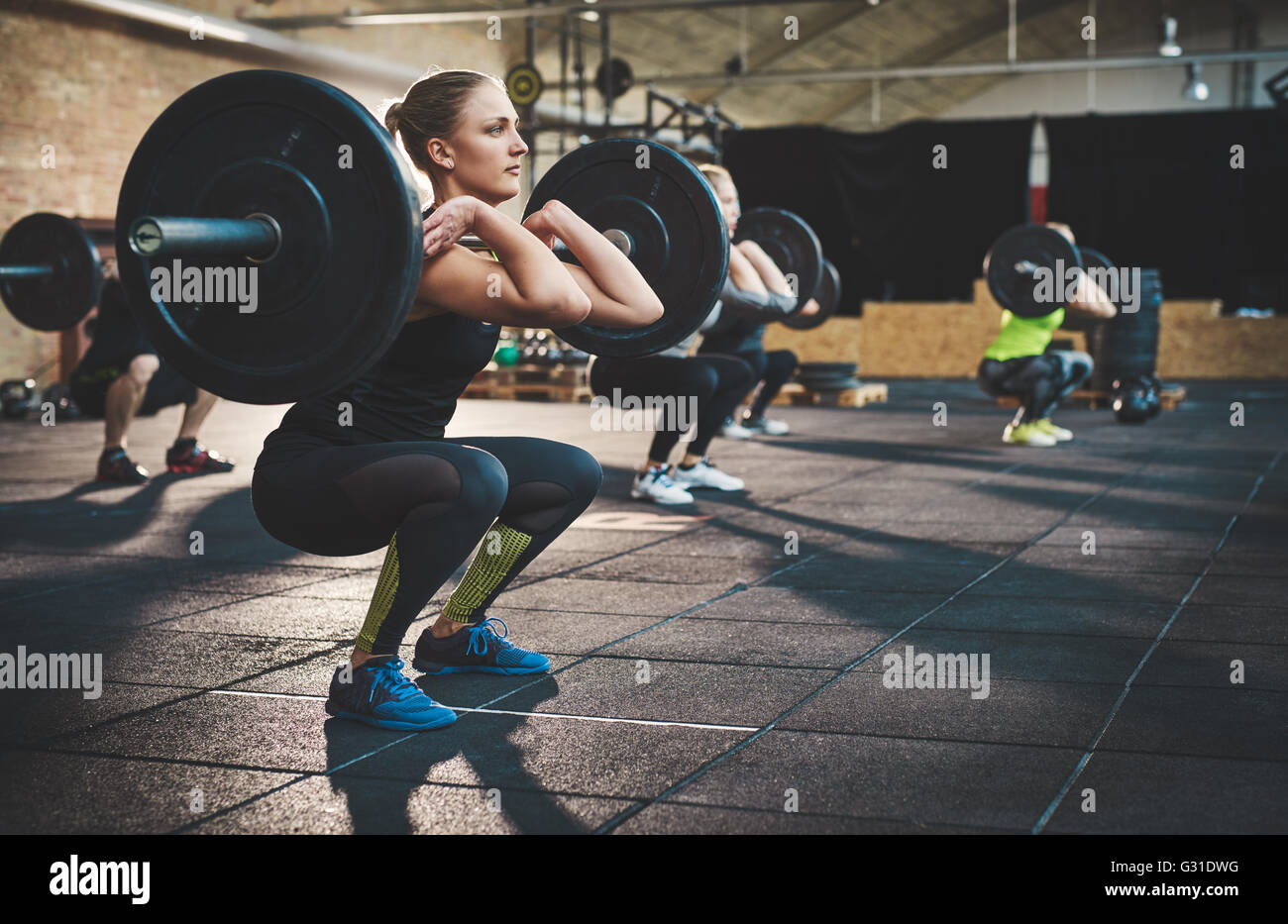 Fit young woman lifting barbells looking focused, working out in a gym with other people - Stock Image